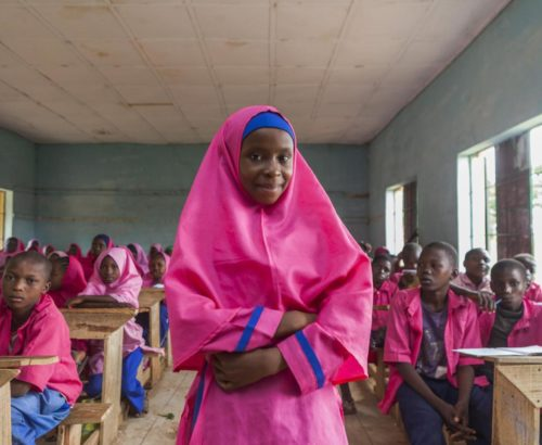 "Nailatu Al-Quasm, 12, stands in her classroom at Gyezmo primary school in the town of Toro, Bauchi State. Other students are nearby. Their school is among the beneficiaries of the Girls' Education Project (GEP). Led by the Government with support from the United Kingdom's Department of International Development (DFID) and UNICEF, the GEP aims to get 1 million more girls into school by 2020, while at the same improving the quality of education. The project also calls for the deployment of more than 10,000 female teachers to rural areas, where the predominance of male teachers deters many parents from sending their girls to school. Nailatu enrolled in school during the GEP's kick off in Bauchi. Her father, Kasimu Limon Toro, who now runs a traditional Koranic school in a hut near the family's home, did not learn to write until he attended adult literacy classes, but he insists that all his 15 children ""including the 11 girls"" must get a good education. ""I will support her in this with all my heart, until the day I die,"" he said of Nailatu's dreams of becoming a doctor. ""I want to help people. I want to help my mother, my father, my brothers, my sisters,"" said Nailatu."