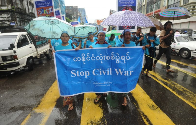 Myanmar people hold a banner reading