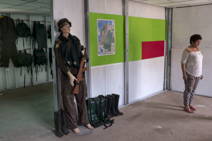 Picture of mannequin in army attire and woman standing nearby