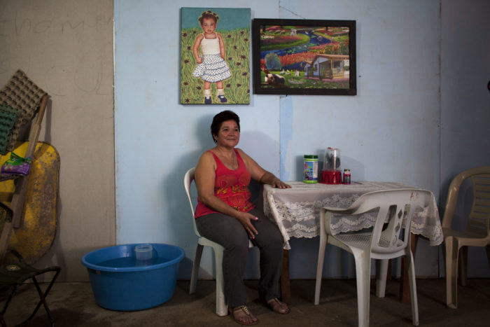 Picture of Elisa Castro at a table with two paintings hanging above her