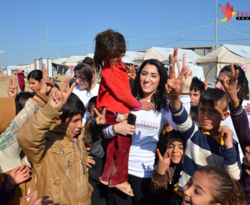 Yezidi woman holding a young girl and surrounded by group of children