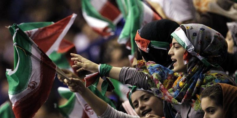 Picture shows a crowd of women waving Iranian flags