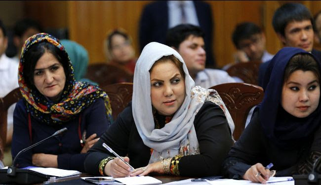 Afghan women taking notes at an event. There is a microphone at their table