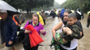 Women and children walk through a flooded street
