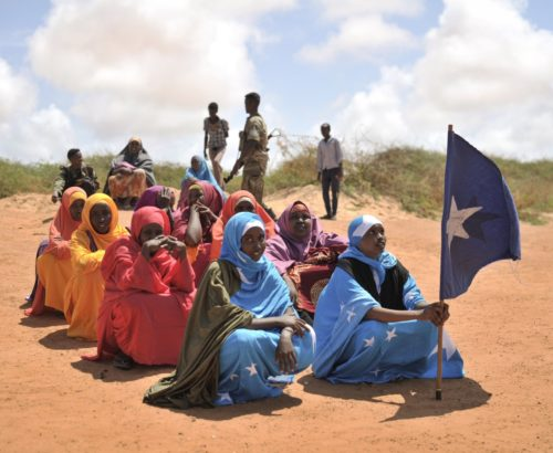 A young woman holds the Somali flag during a demonstration by a local militia, formed to provide security in Marka, Somalia, on April 30. AU UN IST PHOTO / Tobin Jones