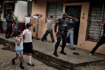 Gang members are apprehended by police, as children watch