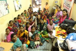 Large group of women in India sitting on a floor