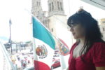 Woman next to Mexican flags