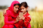 Mother and daughter of Indian ethnicity sitting in the field of wheat crop during summer season using smartphone.