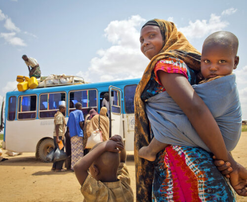 Refugee woman shown carrying a child on her back