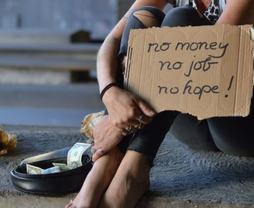 Image of a homeless woman with a sign that says