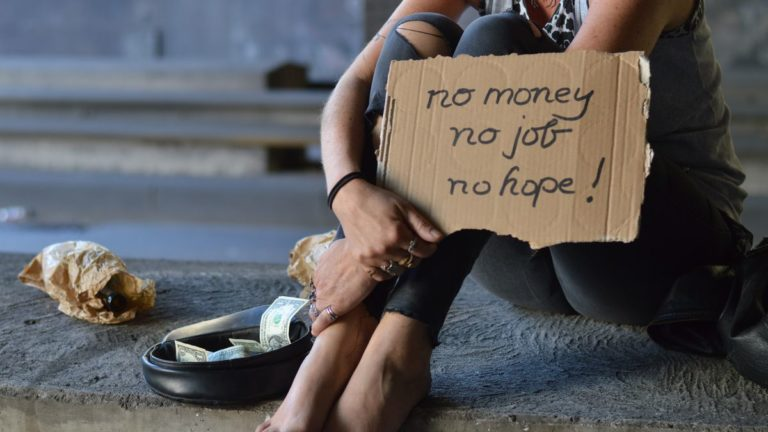 """Image of a homeless woman with a sign that says """"No money, no job, no hope."""""""
