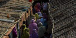 Veiled women walking between huts