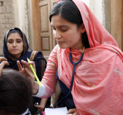 A female doctor examines a patient.