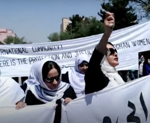 A group of Afghan women march in the street holding a large sign.