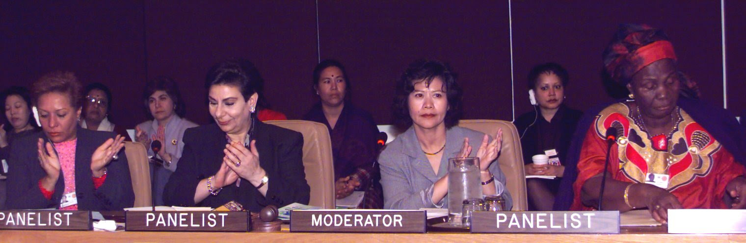 An image of four women sitting on a panel for speakers at a formal negotiation.