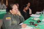 A women wearing a Colombian military uniform sits at a table holding a pen while taking notes on a notepad.