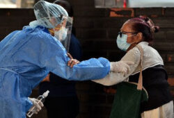Photo of two women wearing medical masks and personal protective equipment holding one another by the forearm.