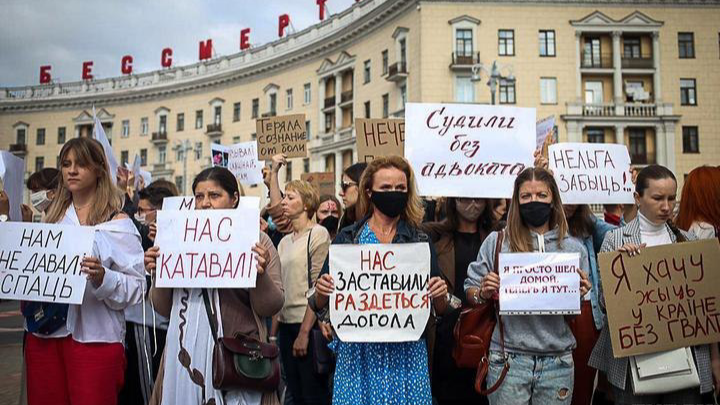 Women in Belarus stand in the streets holding protest signs