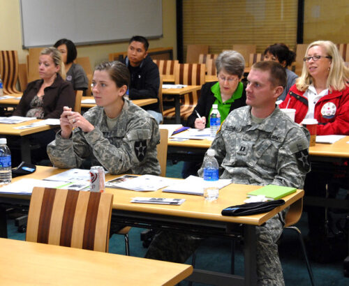 A photo of U.S. soldiers and family members sitting at desks in an International Humanitarian Law class held by the Red Cross.