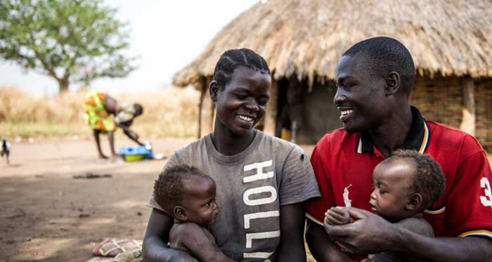 A man and woman smile at one another while each holding a small child.