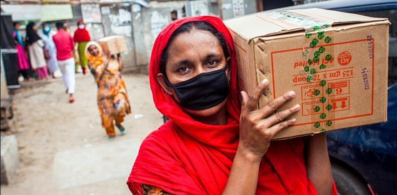 Photo of a woman wearing a face mask and carrying a box over her shoulder.