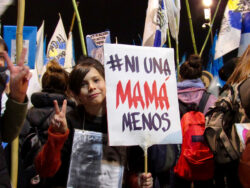 """Photo of a young person holding a sign that reads """"Ni una Mama menos"""" at a protest in Buenos Aires, Argentina."""