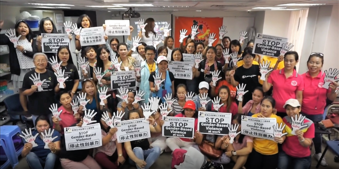 """A group of women in Honk Kong hold signs that read """"stop gender-based violence at work"""""""