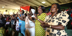 photo shows several women standing side-by-side and clapping in unison