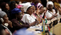 A photo of women participating in a formal peace process echoes the theme of the event.