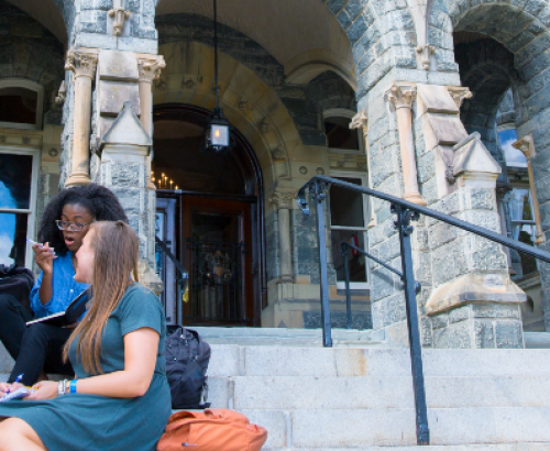A decorative photo shows Georgetown students sitting on stairs outside a building on campus speaking among one another in a diverse group.