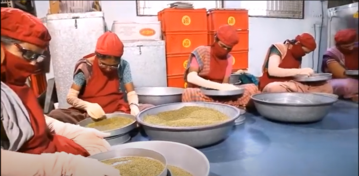 A decorative image shows women wearing face masks sorting grain in large bowls. The women are self-employed farmers affiliated with SEWA, the organization featured in this article.