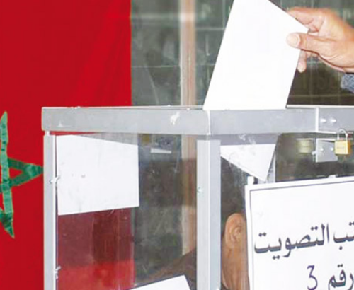A decorative image shows a person dropping a ballot into a ballot box in front of a flag of the country of Morocco, which illustrates the topic of political power in Morocco discussed in the article published on this page.