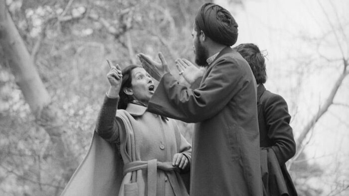 An image of a woman wearing modern clothing speaking with a man during the Iranian Revolution is included to give a visual representation of how women advocated for their rights at the time.